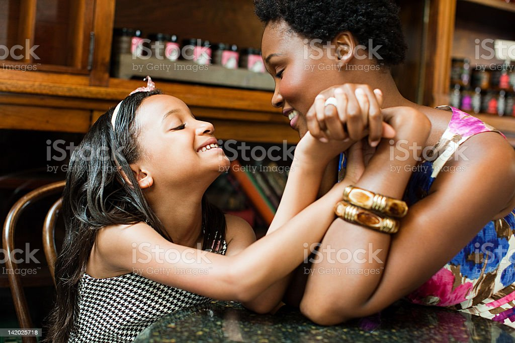 Mother and daughter holding hands in cafe stock photo