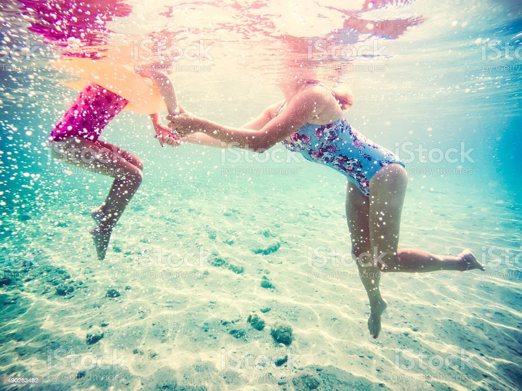 Mother and daughter holding hands in sea together stock photo