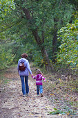 Mother and daughter holding hands walking in the woods