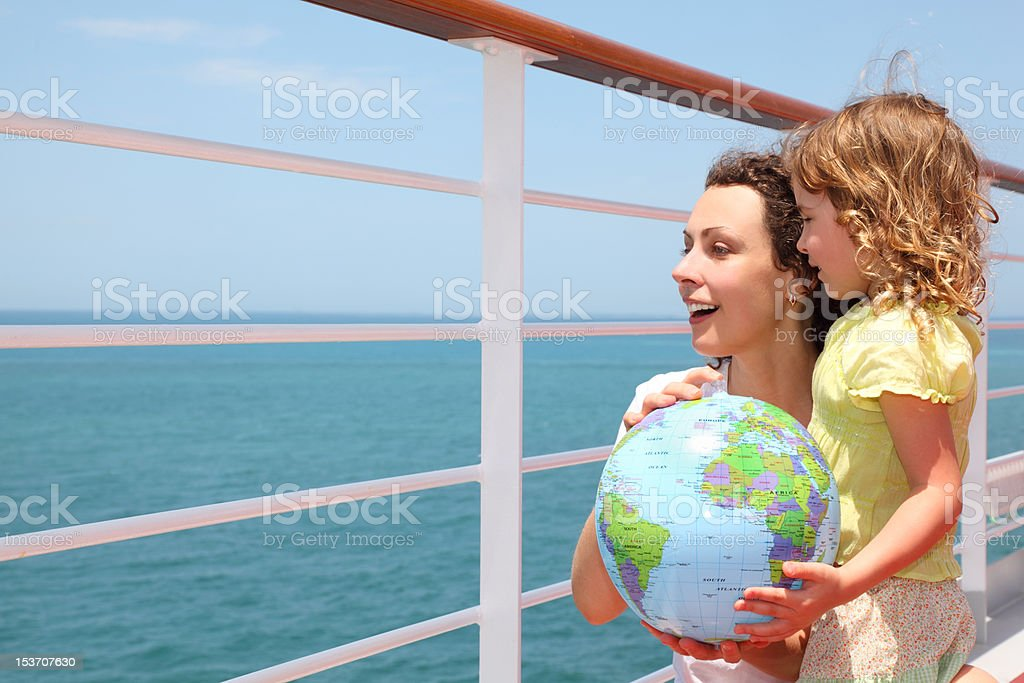 Mother and daughter holding inflatable globe on cruise liner deck royalty-free stock photo