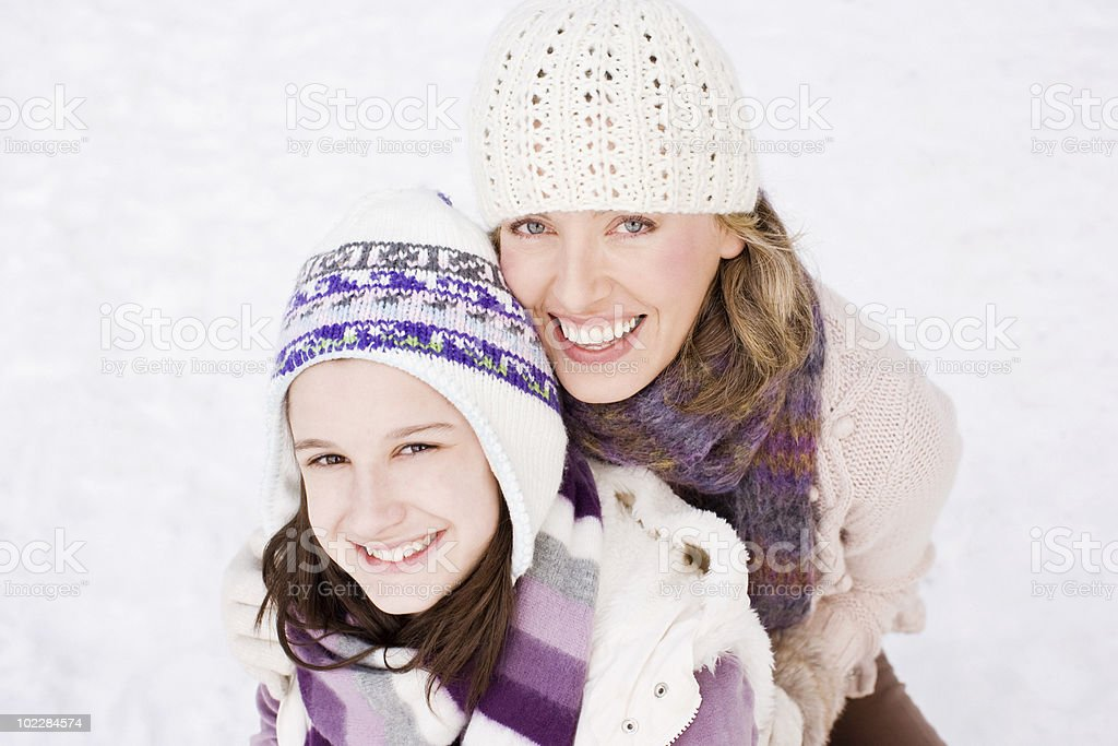 Mother and daughter hugging outdoors in snow royalty-free stock photo
