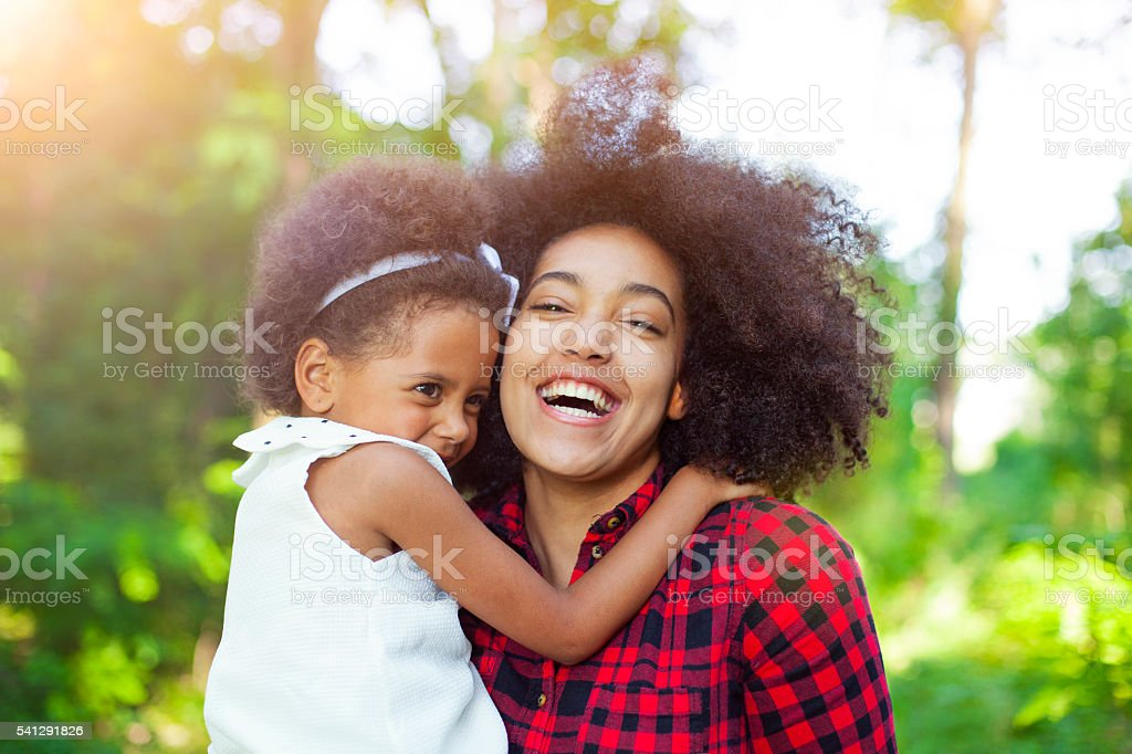 Mother and daughter hugging outdoors stock photo