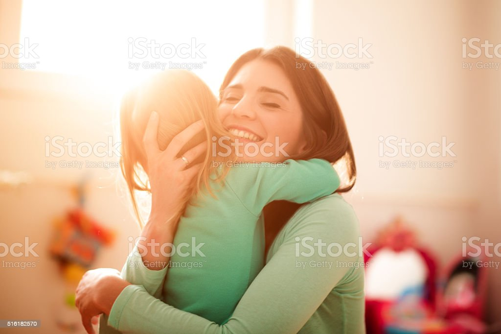 Mother and daughter hugging stock photo