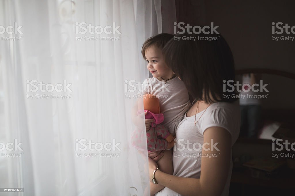 mother and daughter in arms waiting for dad looking out stock photo