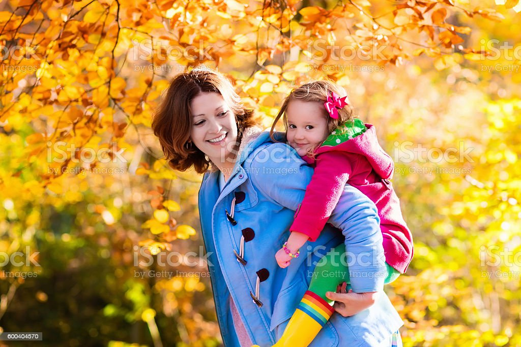 Mother and daughter in autumn golden park stock photo