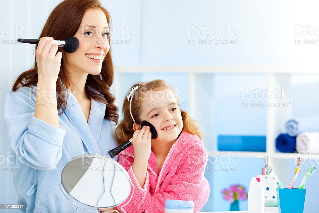 Mother and daughter in bathrobes putting on makeup royalty-free stock photo
