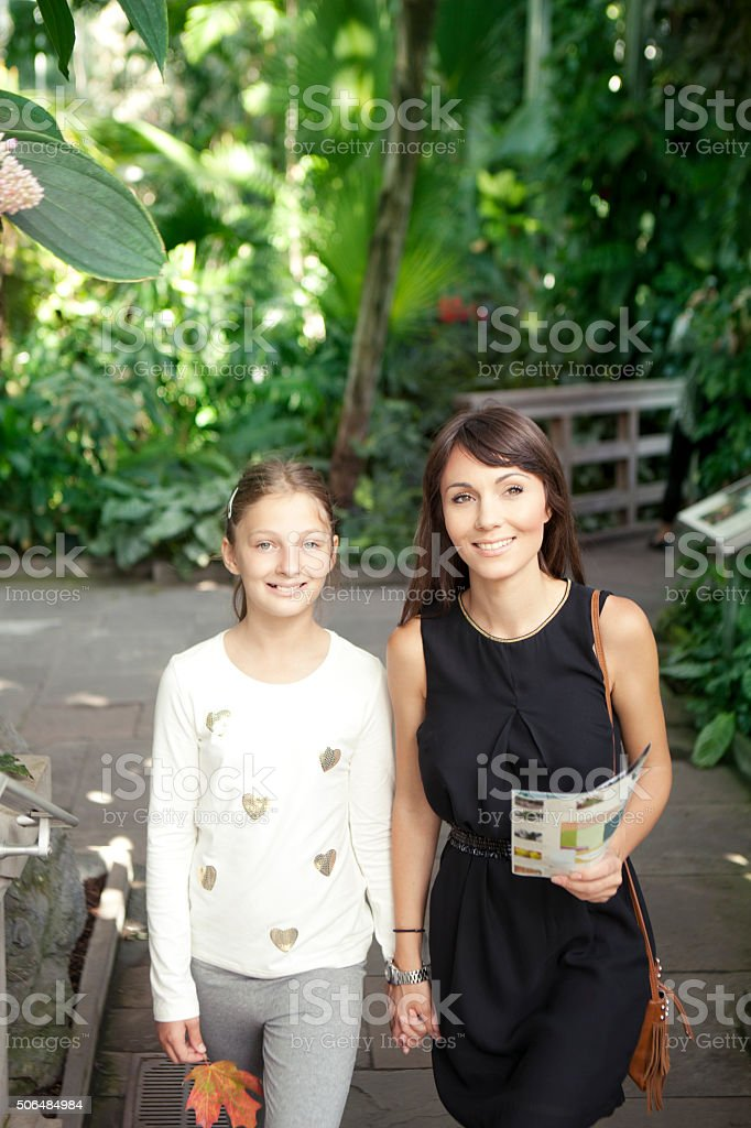 Mother and daughter in botanical garden stock photo