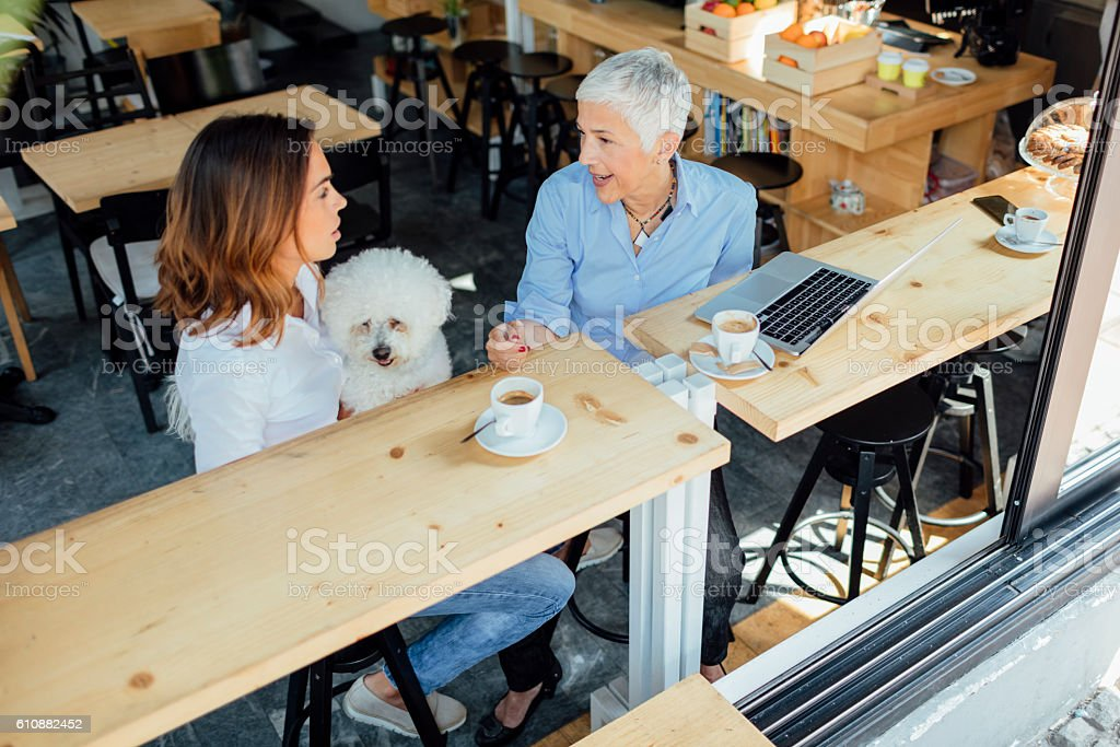 Mother and Daughter In Cafe With Their Dog stock photo