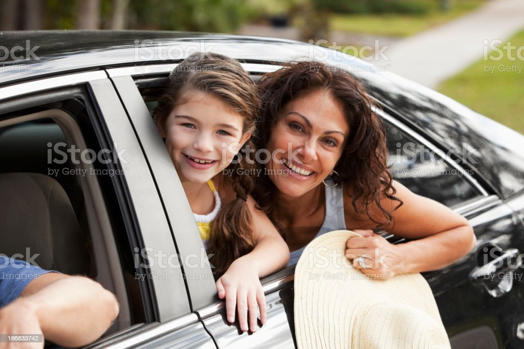 Mother and daughter in car leaning out back window stock photo