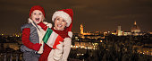 mother and daughter in Christmas hats showing flag, Florence