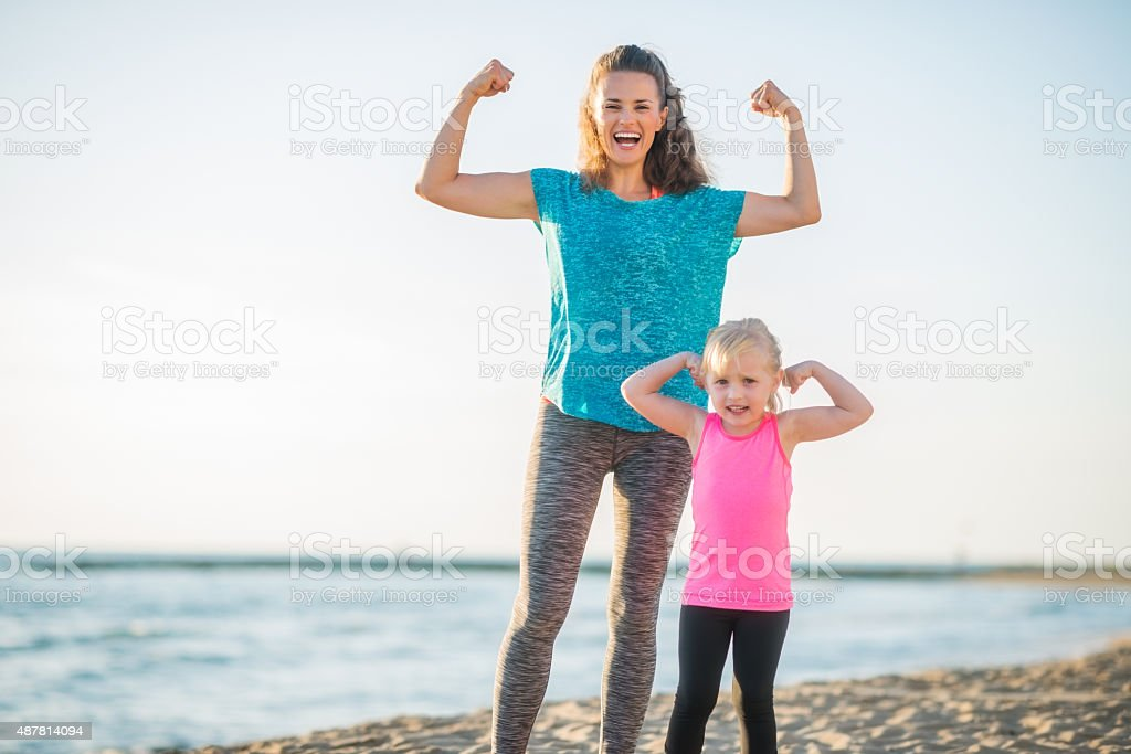 Mother and daughter in fitness gear on beach flexing arms stock photo
