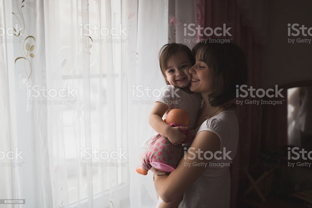 mother and daughter in his arms waiting for dad looking stock photo