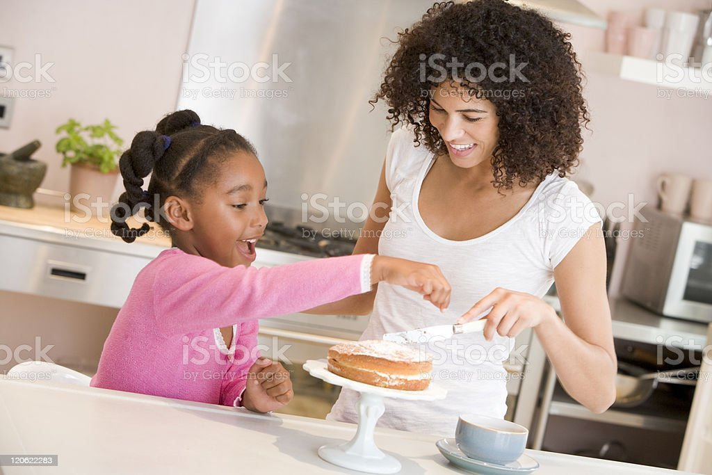 Mother and daughter in kitchen icing a cake smiling stock photo