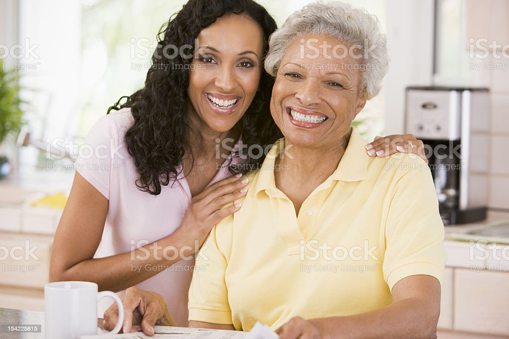 Mother and daughter in kitchen smiling stock photo