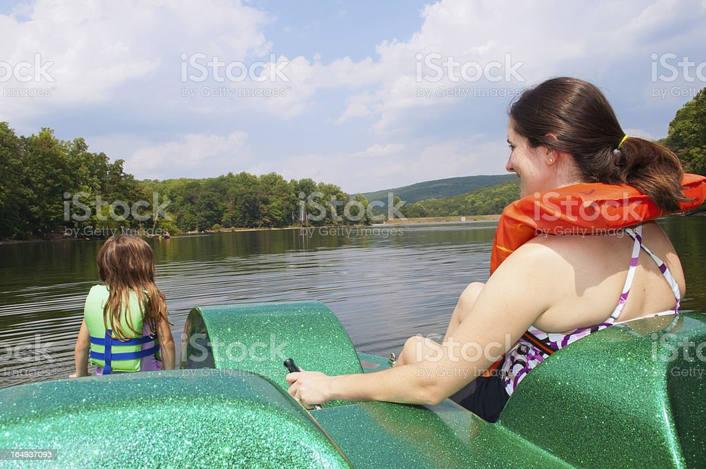 Mother and daughter in paddle boat on moutain top lake stock photo