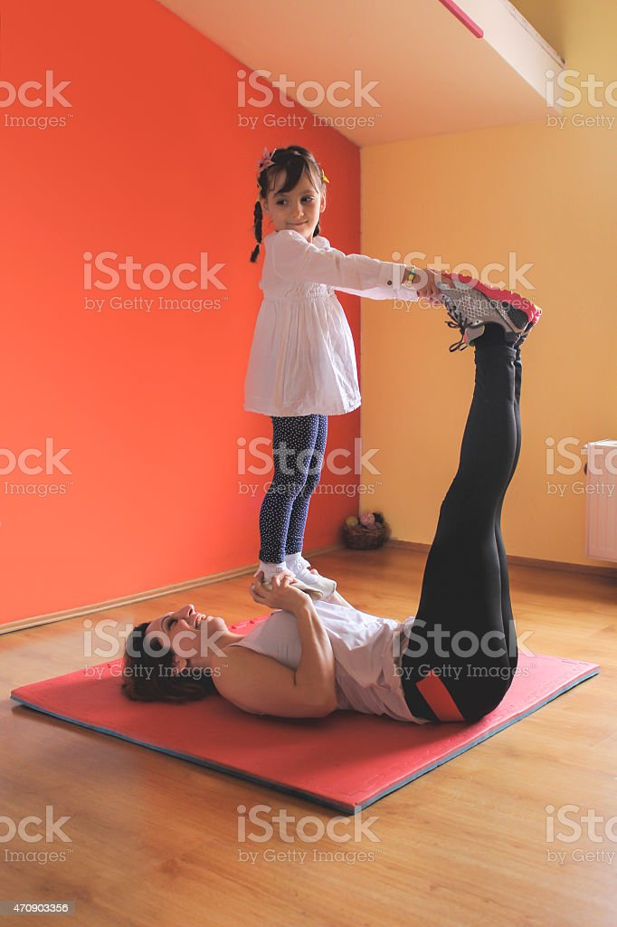 mother and daughter in pilates exercise stock photo