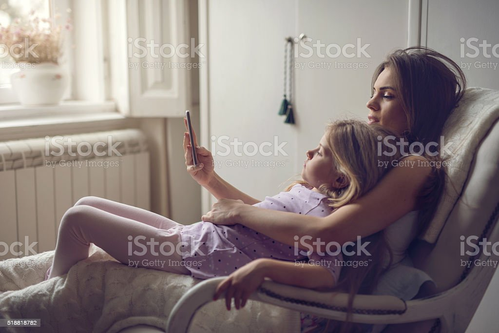 Mother and daughter in rocking chair using mobile phone. stock photo