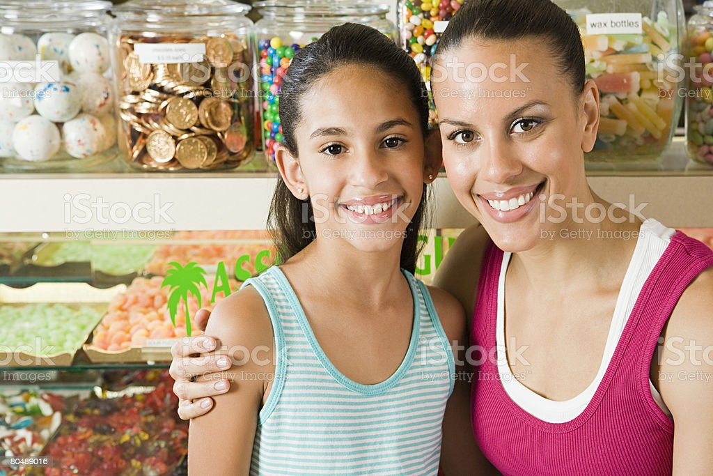 Mother and daughter in sweet shop stock photo