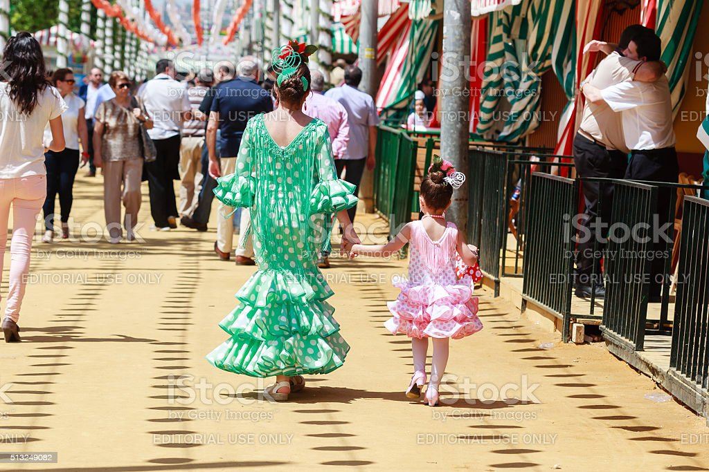 Mother and daughter in traditional dress walking alongside Casetas stock photo