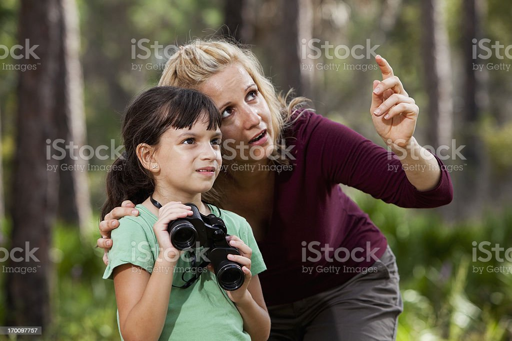 Mother and daughter in woods with binoculars stock photo