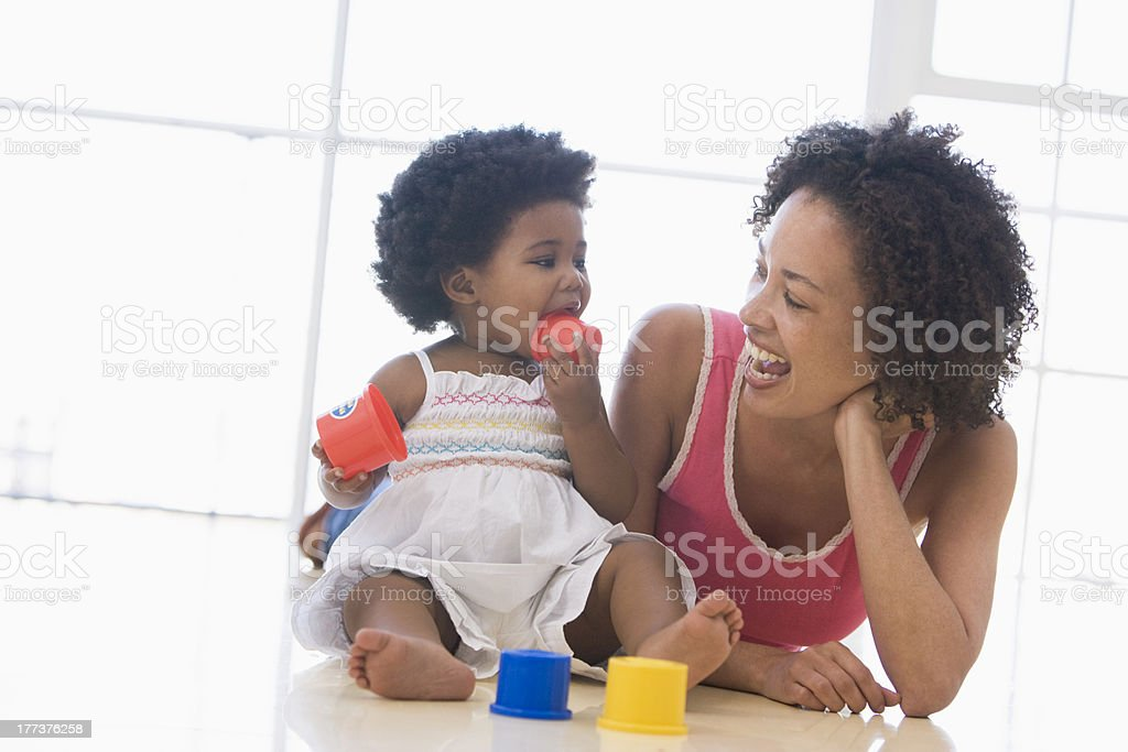 Mother and daughter indoors playing stock photo