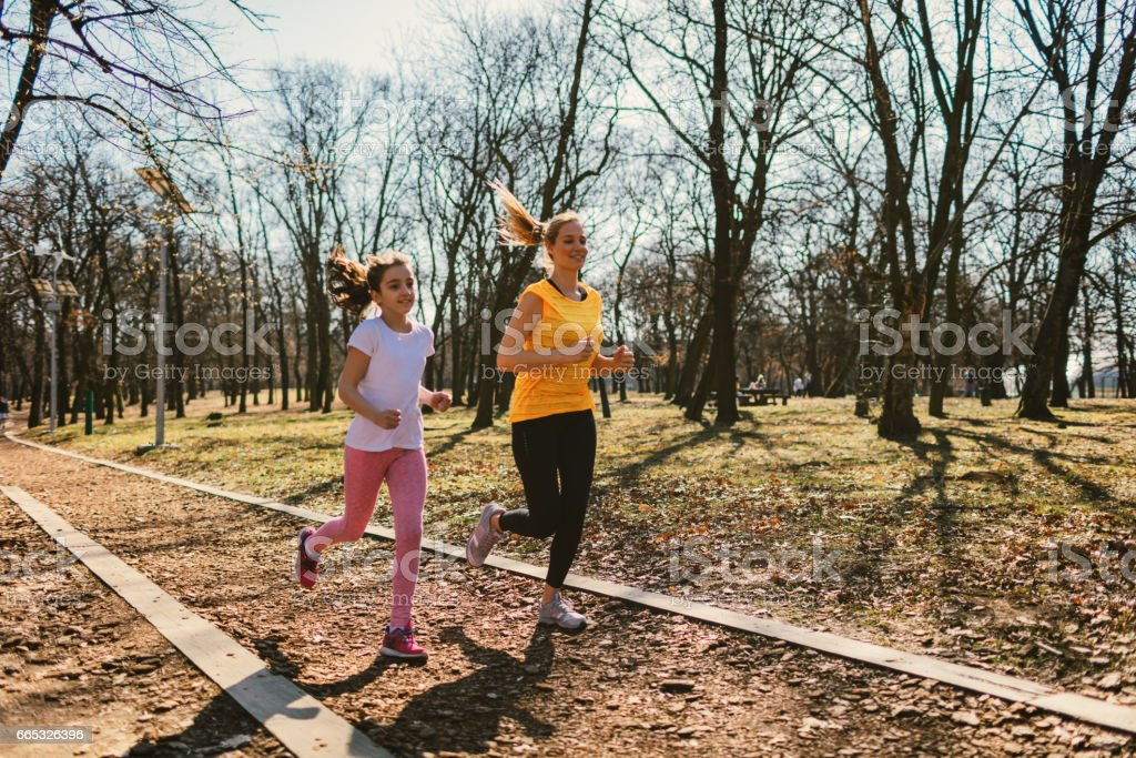Mother and daughter jogging outdoors stock photo