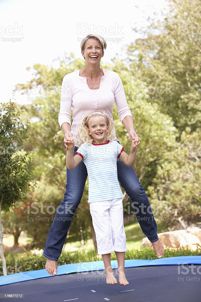 Mother And Daughter Jumping On Trampoline In Garden stock photo