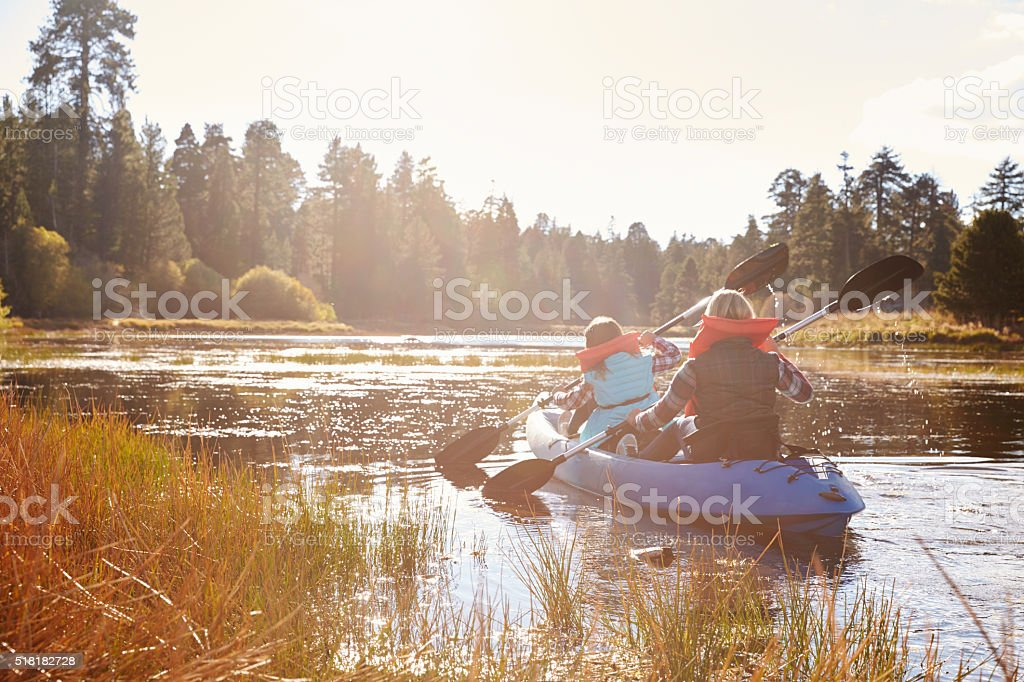 Mother and daughter kayaking on lake, back view stock photo