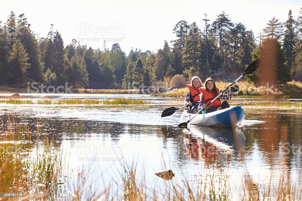 Mother and daughter kayaking on lake, front view stock photo