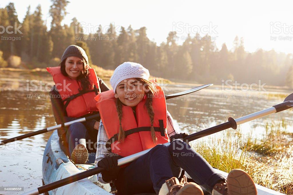 Mother and daughter kayaking on rural lake, close up stock photo