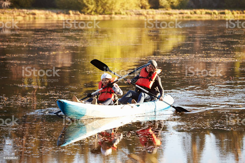 Mother and daughter kayaking together on a lake, close up stock photo