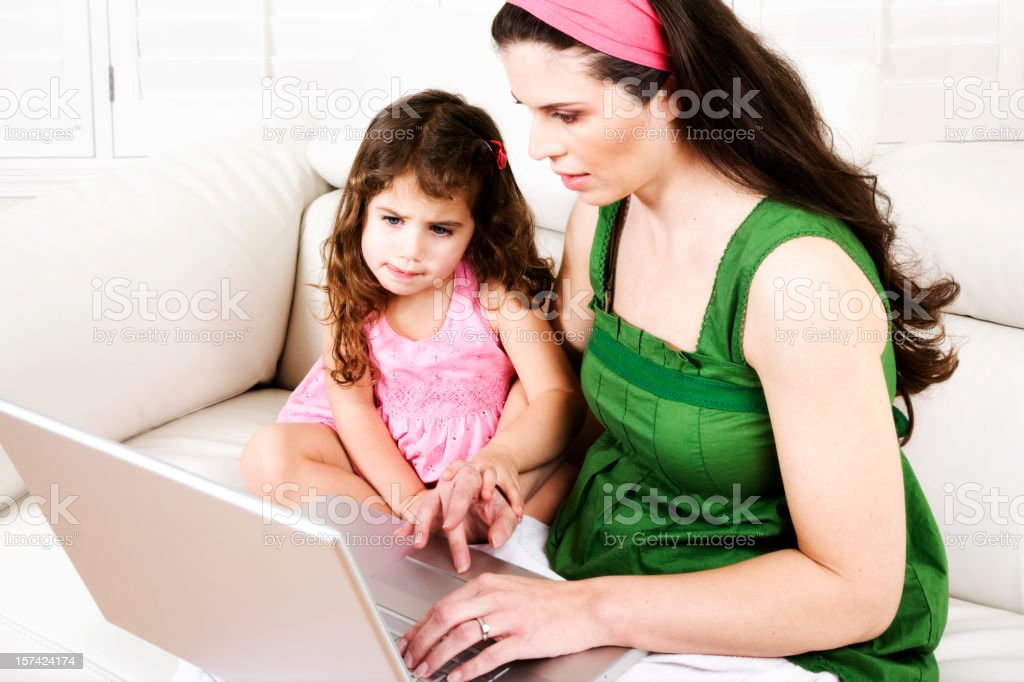 Mother and Daughter laptop computer home leather couch learning royalty-free stock photo