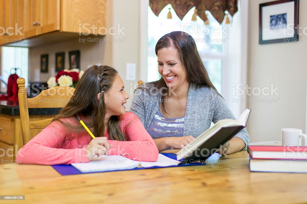 Mother and daughter laugh about something they just learned stock photo