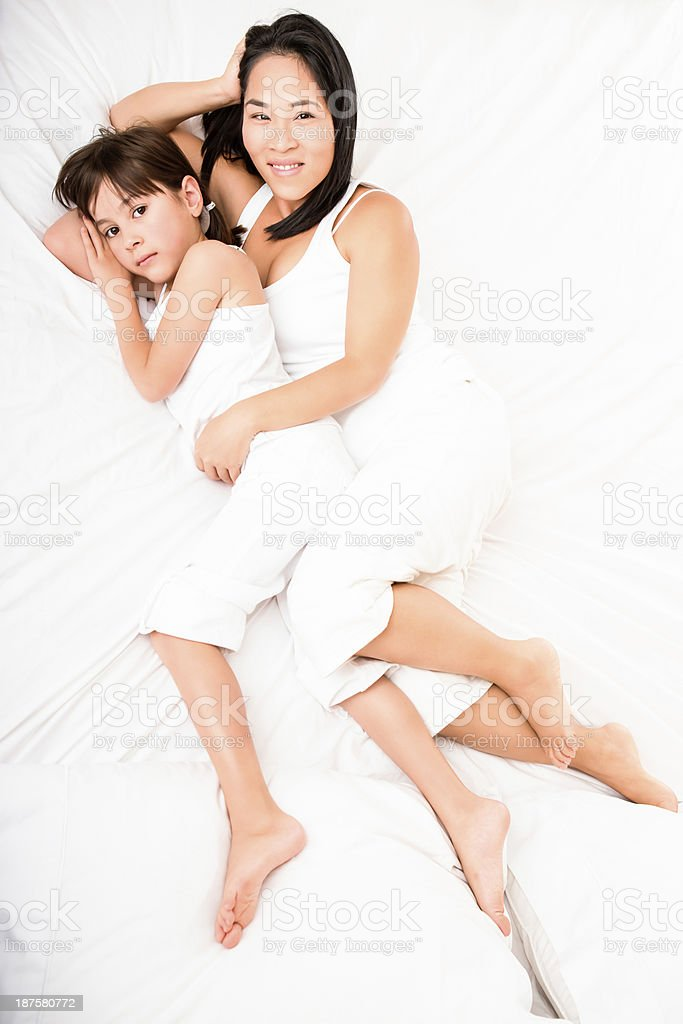 Mother and daughter laying in bed royalty-free stock photo