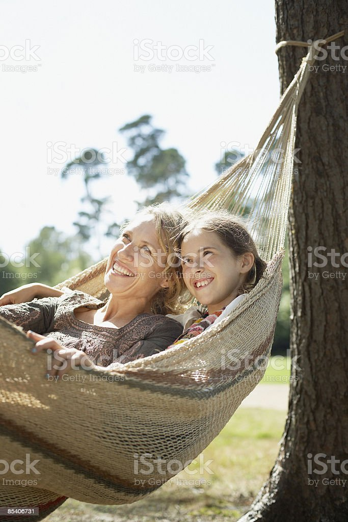Mother and daughter laying in hammock stock photo