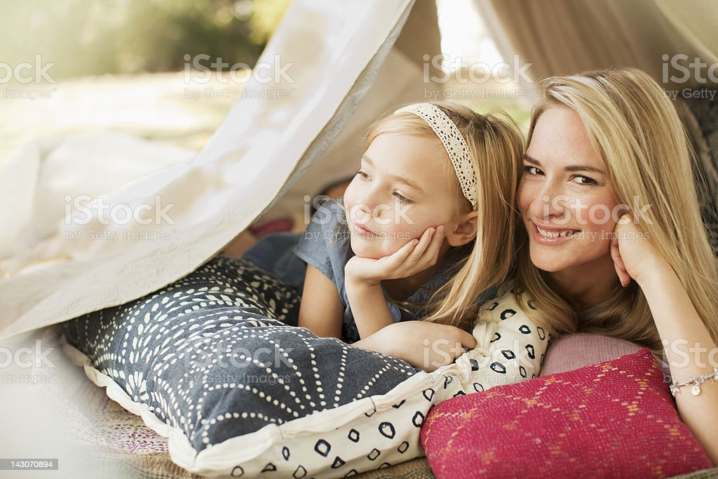Mother and daughter laying in tent outdoors royalty-free stock photo