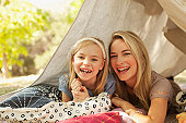 Mother and daughter laying in tent