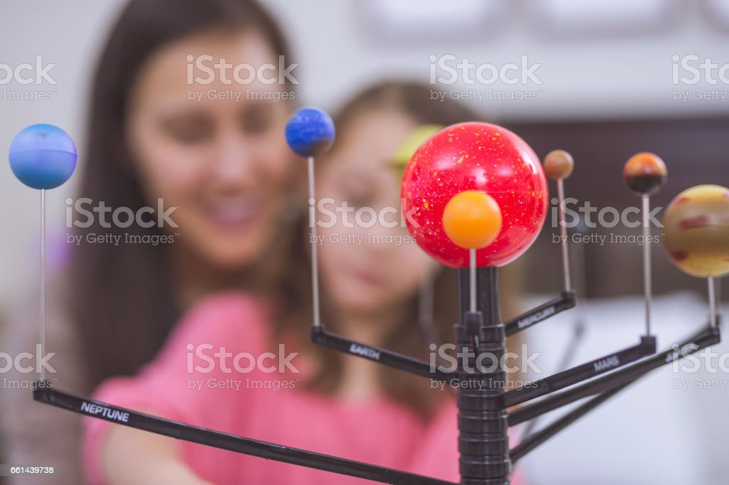 Mother and Daughter learning about astronomy together with model of planets stock photo