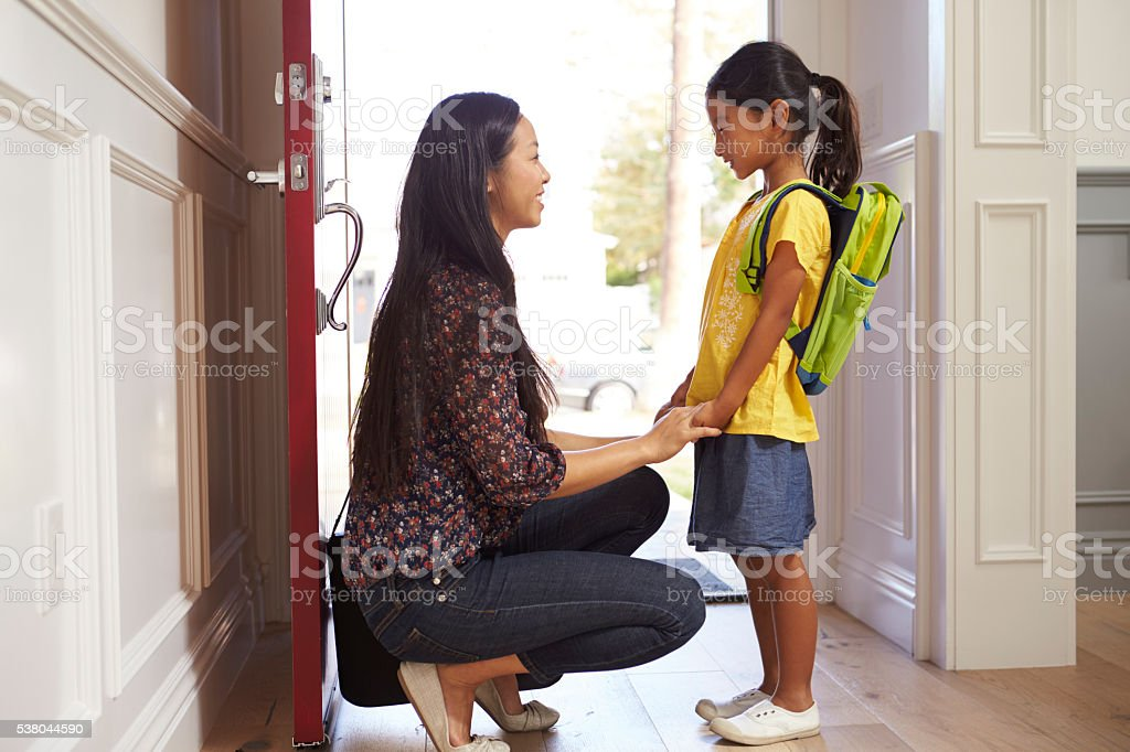 Mother And Daughter Leaving Home For School stock photo