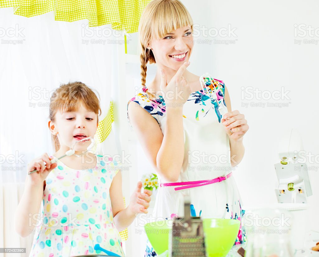 Mother and daughter lick whipped cream in a kitchen. royalty-free stock photo