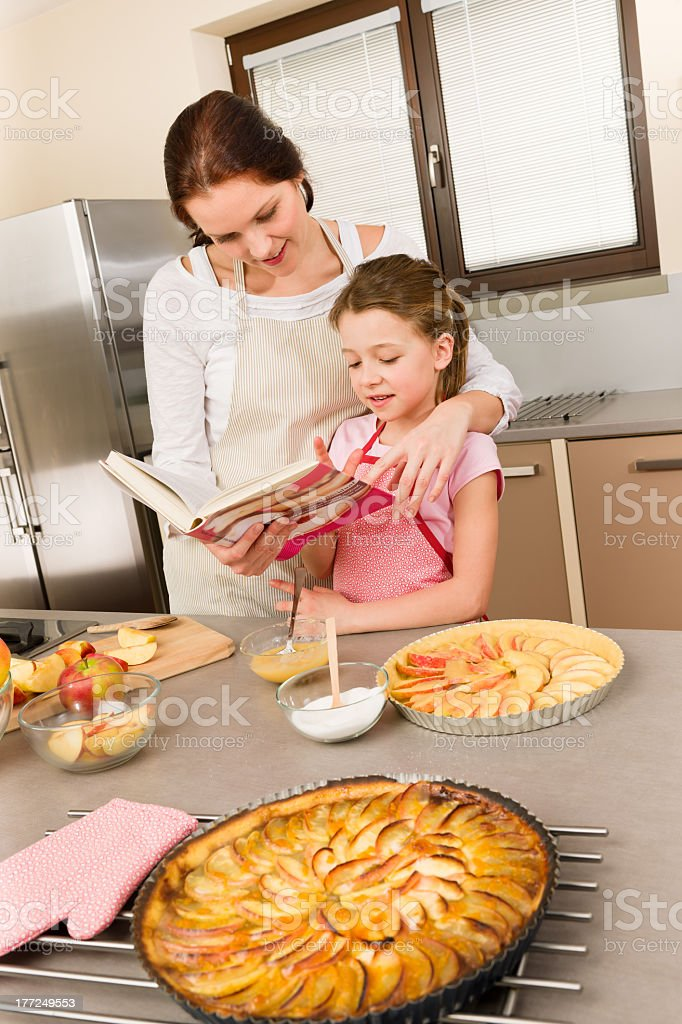 Mother and daughter look baking cookbook royalty-free stock photo