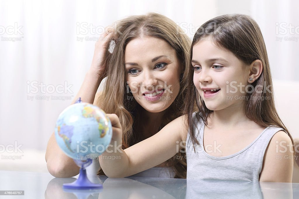 Mother and daughter looking at a globe royalty-free stock photo