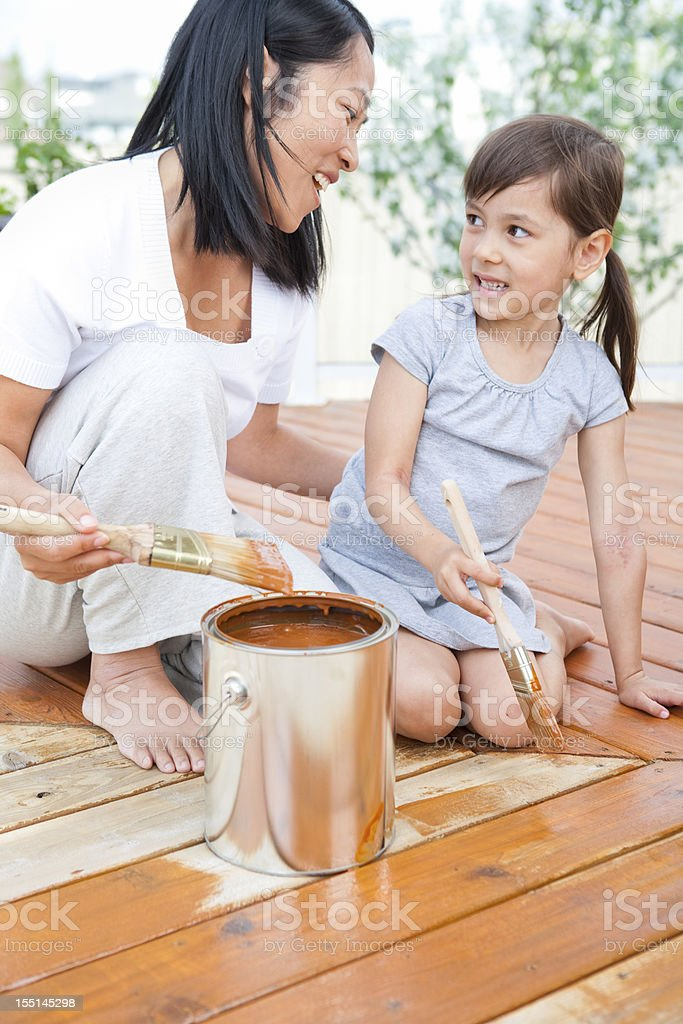 Mother and daughter looking at each other while painting royalty-free stock photo