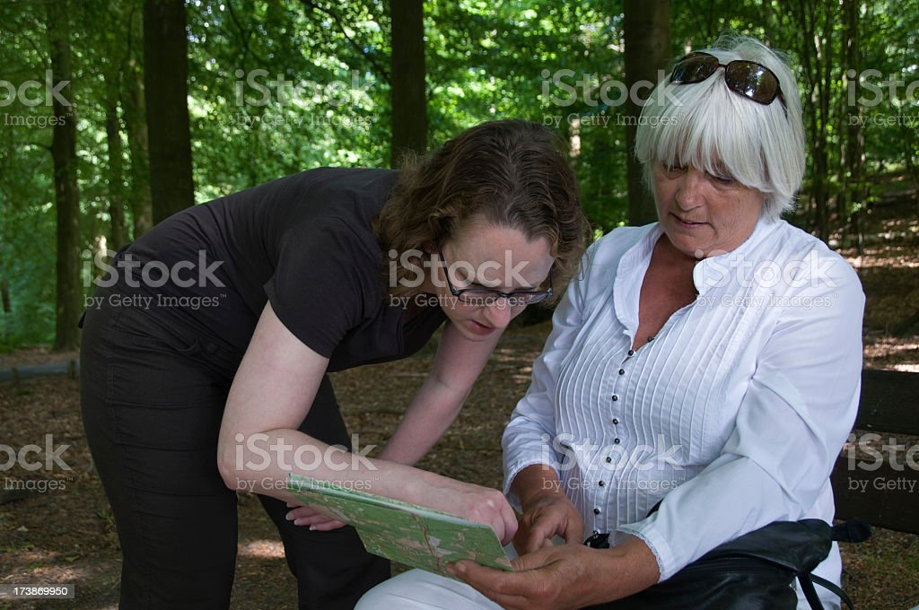 Mother and daughter looking at map outdoors in wood stock photo