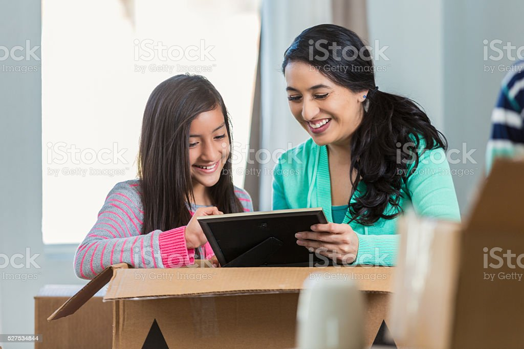 Mother and daughter looking at photo while packing stock photo