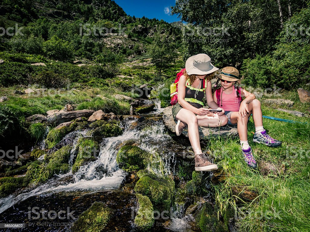 Mother and daughter looking at smartphone during trekking break stock photo