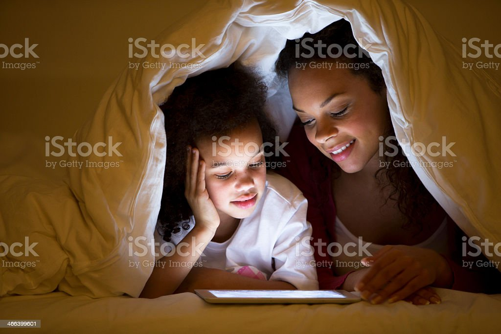 Mother and Daughter lying in bed stock photo