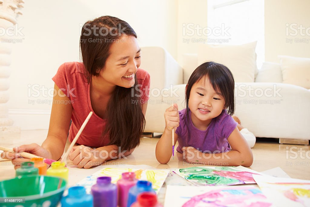 Mother And Daughter Lying On Floor And Painting Picture stock photo