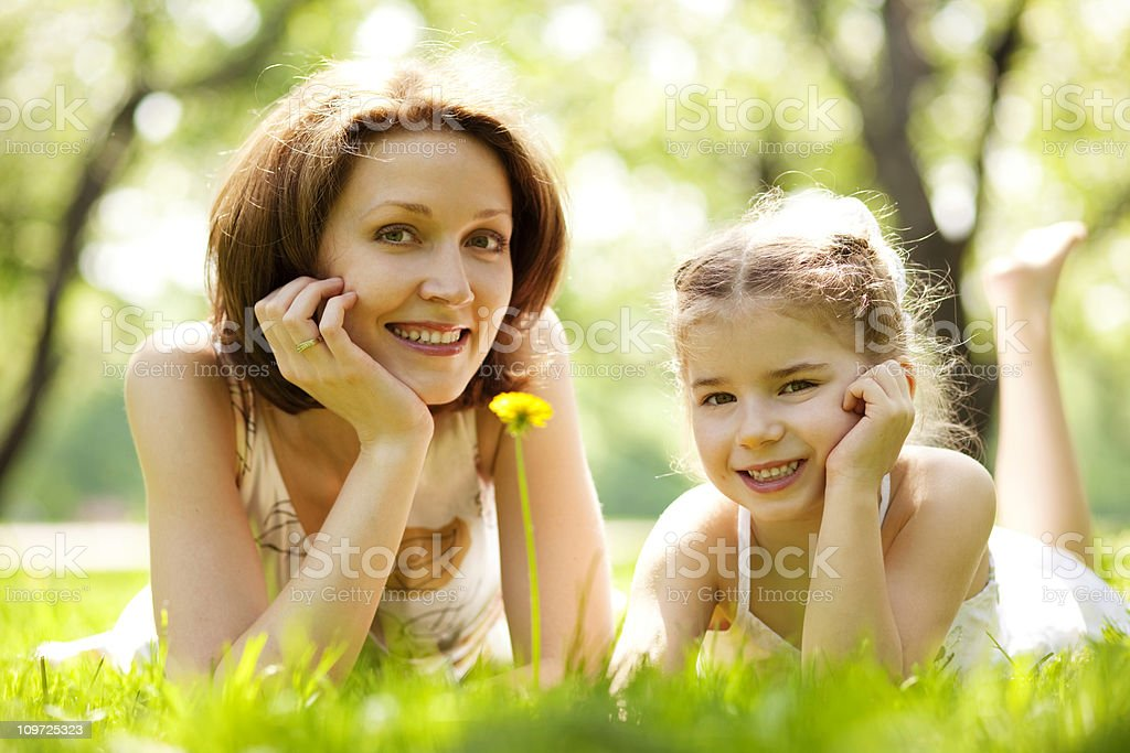 Mother and daughter lying on grass in park royalty-free stock photo