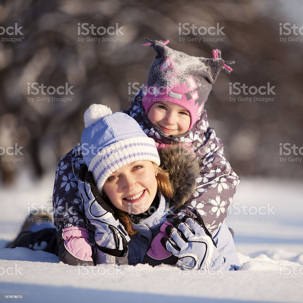 Mother and daughter lying on snow royalty-free stock photo